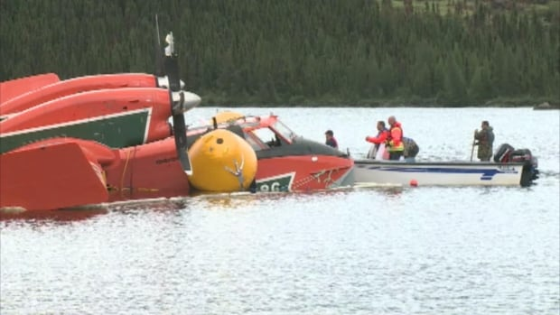 Government workers survey the wreckage of a water bomber that crashed and sank in Moosehead Lake in July 2013. The plane was brought to the surface days later.