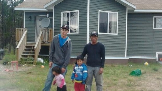 John McKay poses with his nephew and two young children in front of their home on the Salt River First Nation in Fort Smith, N.W.T. McKay was given an eviction notice for Friday evening, but the family is still in the home.