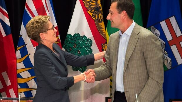 Ontario Premier Kathleen Wynne and P.E.I. Premier Robert Ghiz shake hands at the closing news conference of the annual Council of the Federation meeting in Charlottetown on Aug. 29, 2014.