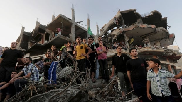 Palestinians attend a victory rally organized by the military wing of Hamas, at the debris of destroyed houses in the northern Gaza Strip.
