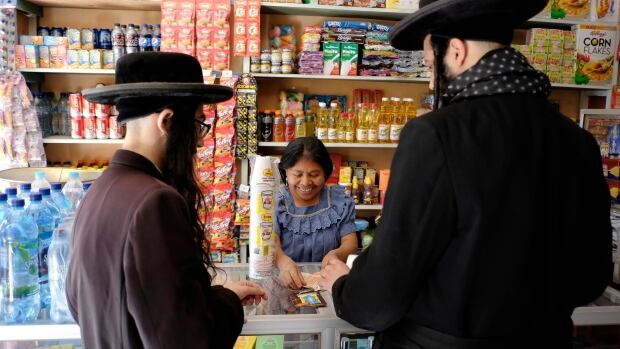 Men from Lev Tahor shop at a store in the village of San Juan La Laguna Aug. 24, 2014. They moved to Guatemala City after the village's Elders' Council expelled Lev Tahor.