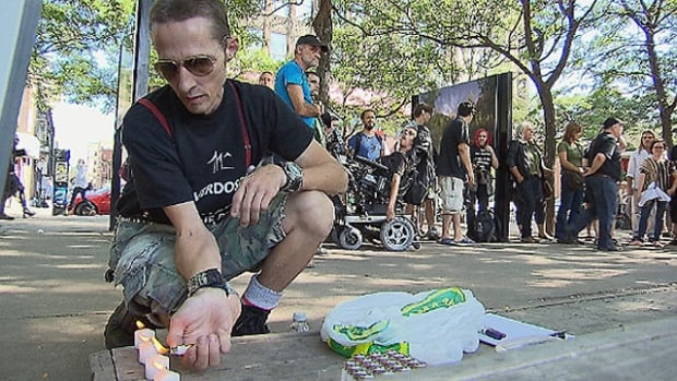 A man lights candles for the people who died over the summer from drug overdoses.