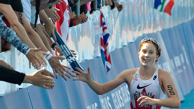 Paula Findlay of Canada is congratulated by her hometown Edmonton fans as she finishes the Elite Women Championship at the ITU World Triathlon Grand Final on Saturday.