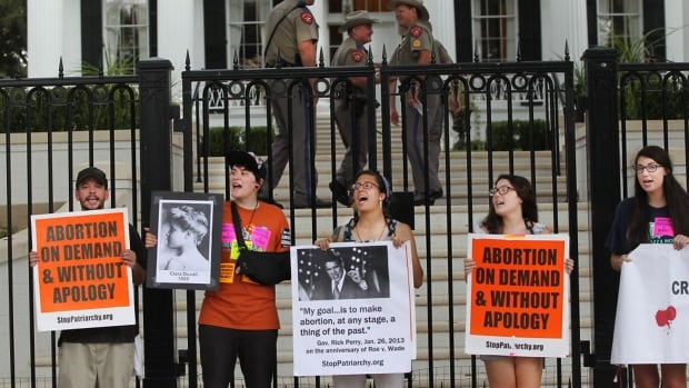 Abortion rights supporters take a stand outside the governor's mansion Friday after a federal judge in Austin, Texas, struck down 2 provisions of a 2013 Texas law that restricts abortions.