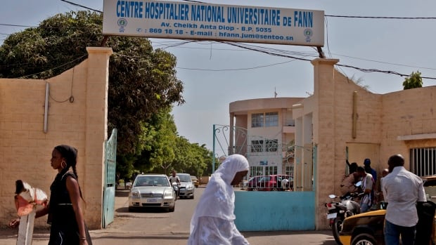 Women walk past the entrance to the University Hospital Fann in Dakar, where a man is being treated for symptoms of the Ebola virus. The 21-year-old student from Guinea is the country's first confirmed case of the virus that is plaguing several countries in West Africa and has so far killed around 1,500 people.