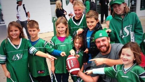 Defensive Lineman David Lee celebrated the return of his ball from the Winnipeg Blue Bombers with some young fans at Riders Fan Day on Saturday.