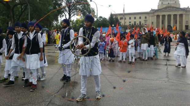 Members of Manitoba's Sikh community gather outside the provincial legislature in Winnipeg to celebrate the 410th anniversary of the creation of Sikhism's holy book.