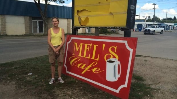 Mylinda Isaac stands next to her restaurant sign just after it was torn down Saturday on Saskatoon's west side.