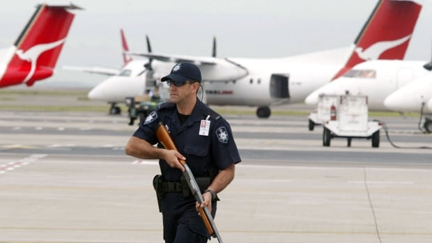 A file photo from 2003 shows an armed Australian Federal Police officer at Sydney Airport, overseeing the transport of accused North Korean drug smugglers. Australia's ongoing crackdown on the illegal drug trade means that the high-risk market is also highly lucrative, and more and more drug runners from Canada have been trying to capitalize on that potential for profit.