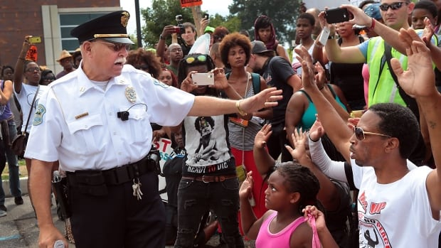 Ferguson Police Capt. D. McBride orders protesters back to the sidewalk at a demonstration in front of the police station in Ferguson on Saturday. Police officers in Ferguson have begun wearing body cameras after weeks of unrest over Michael Brown's shooting.