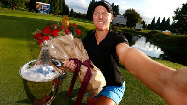 Austin Ernst imitates a selfie with the trophy after defeating I.K. Kim in a one-hole playoff to win the LPGA Portland Classic at the Columbia Edgewater Country Club in Portland.