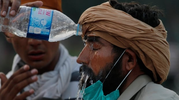 A protester pours water on his colleague suffering from tear gas fired by police to disperse them during a clashes near the prime minister's home in Islamabad, Pakistan on Sunday, Aug. 31, 2014.