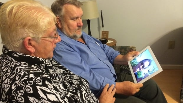 Rose Macisaac and John MacNeil look at a picture of their brother Kenny. They reported him missing Wednesday after he failed to return to his home in Upper Leitches Creek.