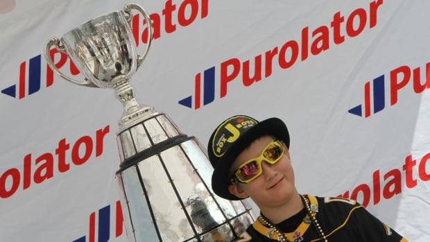 Ticats fan Lucas Morrow, 9, poses for a photo with the Grey Cup before Hamilton played the Toronto Argonauts in September.