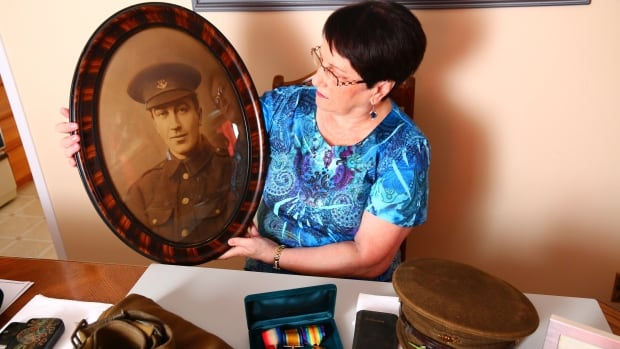 Diana Snow of St. John's holds a portrait of her grandfather, William Newell, one of the First 500 volunteers who signed up to fight in the First World War. On the table in front of her is what remains of her grandfather's original military kit.
