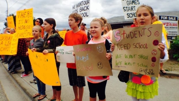 Some students chant 'we want school' outside Premier Christy Clark's MLA office in West Kelowna, B.C.,  on Tuesday morning, as part of the #MLAplaydate protest.