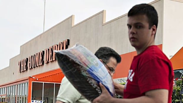 Theo Chronis, right, and his dad Jim Chronis load bags of mulch into their vehicle at a Home Depot store. The retailer says 56 million cards may be affected by its security breach.