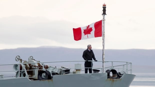 Prime Minister Stephen Harper stands on the bow of HMCS Kingston as it sails in Nunavut's Navy Board Inlet. The bridge of this ship is where the prime minister toasted the search for Sir John Franklin's ships, the Erebus and Terror. They were lost in a 19th century quest to find the Northwest Passage.