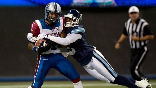 Toronto Argonaut Jermaine Gabriel, right, tries to tackle Montreal Alouettes slotback Arland Bruce as he makes a touchdown catch during first half CFL action in Toronto on Tuesday September 3, 2013.