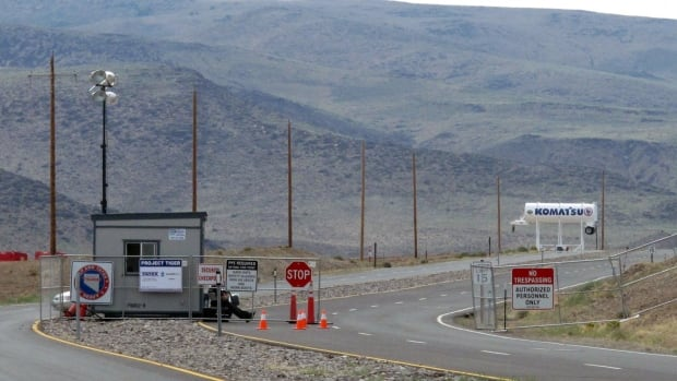 This Aug. 1, 2014 file photo shows security guards at the gate to the Tahoe Reno Industrial Center, about 15 kilometres outside of Reno, Nevada. Tesla Motors has selected the site for its massive factory.