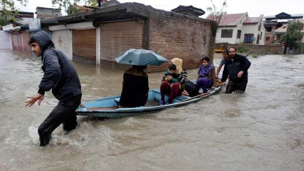 Kashmiri women and a child are transported in a boat through a flooded road to a safer place during incessant rains in Srinagar September 4, 2014.