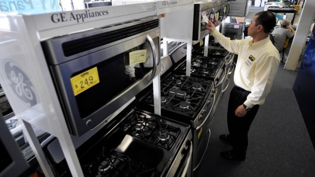 Salesman Hank Pham puts the price on a General Electric (GE) microwave in the appliances section of Howard's Appliance and Big-Screen Superstore in San Gabriel, Calif. Sweden's Electrolux is buying the appliances business of GE for $3.3 billion.