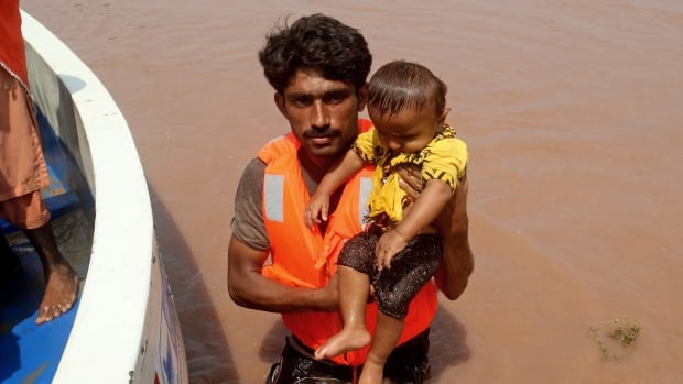 A Pakistani volunteer carries a child rescued from a flooded village in Chiniot, Pakistan. The death toll from floods in Pakistan and India increased on Tuesday as armies in both countries scrambled to help the victims.