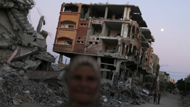 A Palestinian woman walks near the ruins of houses, which witnesses said were destroyed and damaged during the Israeli offensive, in Beit Hanoun town in the Gaza on Sunday.