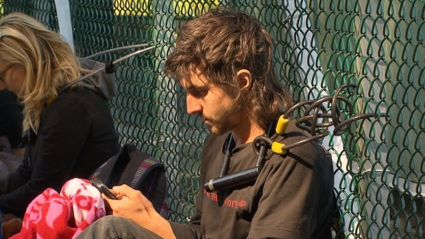 An activist bike-locks himself to the main gate of Kinder Morgan's Westridge Marine Terminal in Burnaby Saturday to protest the company's cutting of trees during survey work for its proposed pipeline expansion.