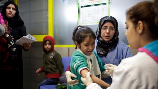 A Syrian girl weeps after receiving the measles vaccine from UNICEF nurses in 2013. Prior to Syria's civil war, some 99 percent of children were 