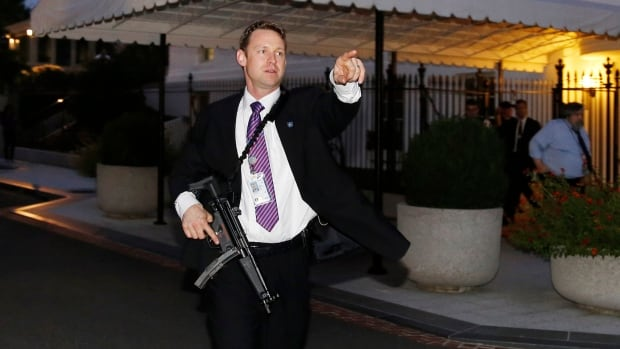 A U.S. Secret Service agent with an automatic rifle hurries people to evacuate the White House complex over a security alert moments after President Barack Obama and his family left for the presidential retreat, Camp David, in Maryland, September 19, 2014.