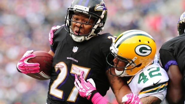 Nike logos and pink gloves representing Breast Cancer Awareness Month are seen in this October 2013 shot of Baltimore Ravens running back Ray Rice (27) being tackled by Green Bay Packers safety Morgan Burnett (42). Rice is at the centre of a domestic violence scandal that has engulfed the NFL and prompted some companies to pull back some of their sponsorship of players and teams.