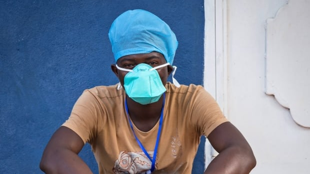 A health care worker takes a rest outside an Ebola isolation unit in Freetown, Sierra Leone, where about 600 people have died of the virus. The U.S. promised Thursday to build new treatment centres in Sierra Leone and Liberia, two of the worst-hit countries.
