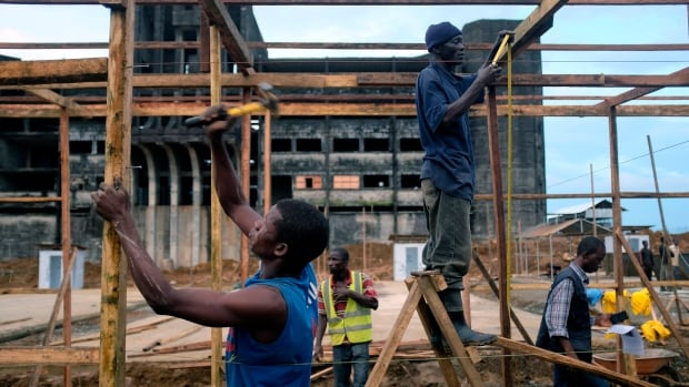 Construction workers build an Ebola isolation and treatment centre in front of a unfinished government building in Monrovia, Liberia, last week. The Ebola virus outbreak has overwhelmed the weak health systems of some of the world's poorest countries.