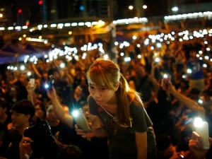Protesters turn on their mobile phone flashlights as they block an area outside government headquarters in Hong Kong on Wednesday, Oct. 1. Thousands of pro-democracy protesters thronged the streets, some of them jeering National Day celebrations, and students threatened to ramp up demonstrations if the city's pro-Beijing leader does not step down.