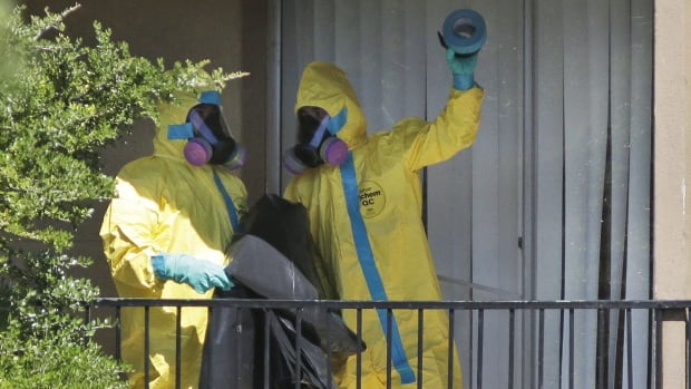 Workers in hazardous-material suits arrive last Friday at a Dallas apartment visited by Thomas Duncan to disinfect its contents.