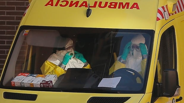 An ambulance with medical staff wearing protective suits and gloves arrives Wednesday at the Madrid apartment of a Spanish nursing assistant infected with Ebola.