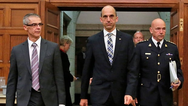 Canada's Public Safety Minister Steven Blaney (C) arrives with Canadian Security Intelligence Service (CSIS) director Michel Coulombe (L) and Royal Canadian Mounted Police (RCMP) Commissioner Bob Paulson to testify before the Commons public safety and national security committee.