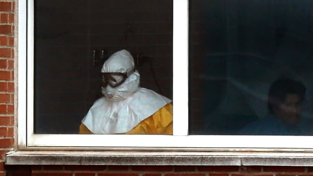 A medical practitioner wearing protective clothing stands next to an isolated patient on the sixth floor of the the Carlos III hospital in Madrid on Thursday. Two doctors who treated a Spanish nurse who contracted Ebola have been admitted to a Madrid hospital for precautionary observation, bringing to six the number being monitored at the centre.