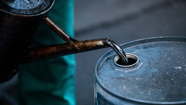 A worker pours oil into a barrel at a European oil refinery earlier this month. Lower crude prices are costing the oil industry and some provinces billions, but should lower costs elsewhere in the economy.