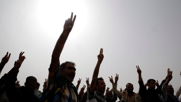 Kurdish mourners flash the V-sign as they sing a nationalistic Kurdish song at a cemetery in Suruc, on the Turkey-Syria border, during the funeral of two Syrian Kurdish fighters, names not available, who were  killed in the fighting with the militants of the Islamic State group in Kobani, Syria, last month.