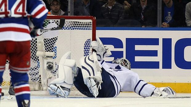 Toronto Maple Leafs goalie James Reimer, right, left Sunday night's game against the New York Rangers after getting clipped in the head.