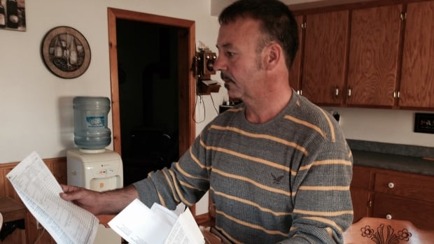 Glenn Apesteguy looks over his papers relating to his injury at Canadian Tire.