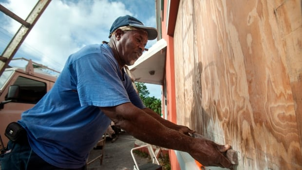 A worker boards up a restaurant as Bermudans prepare for the arrival of Hurricane Gonzalo in Flatts Village. The storm is expected to pass near the island Friday night.