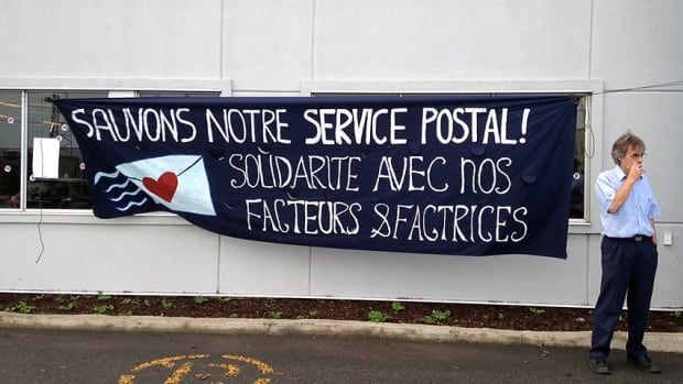 """The sign outside the Repentigny sorting centre reads, """"Save our postal service! Solidarity with our mail-delivery men and women."""""""