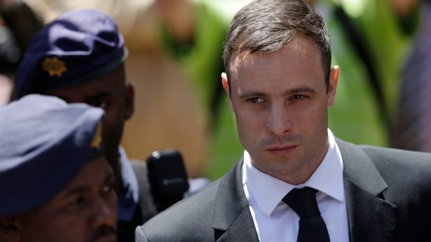 Oscar Pistorius is escorted by police officers as he leaves his sentencing hearing in court in - south-africa-oscar-pistorius-trial