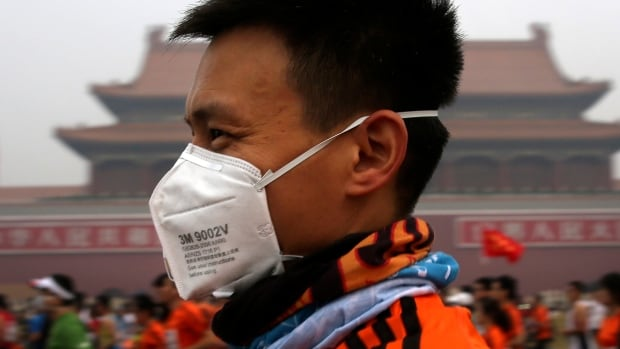 A runner wears a mask to protect himself from pollutants as he jogs past Tiananmen Gate during Sunday's 2014 Beijing International Marathon in Beijing.
