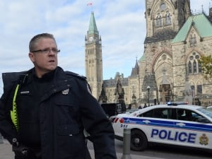 A police officer secures the scene of a shooting on Parliament Hill in Ottawa on Oct. 22, 2014. Nearby, police vehicles surround the National War Memorial after Cpl. Nathan Cirillo, a reservist on duty Wednesday, was fatally wounded in a brazen attack.