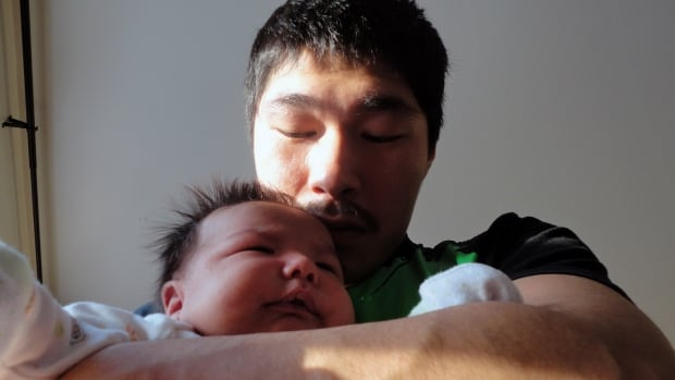 """Luutaaq Qaumagiaq holds his son, Makibi Timilak. """"We need to know why he died to try and help out other Inuit so that they won't have to go through what we went through,"""" he said."""