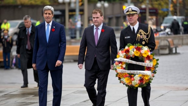 U.S. Secretary of State John Kerry, left, Foreign Minister John Baird and U.S. naval attaché Capt. Charles J. Cassidy walk forward to place a wreath for Cpl. Nathan Cirillo at the Tomb of the Unknown Soldier at the National War Memorial in Ottawa  Tuesday.